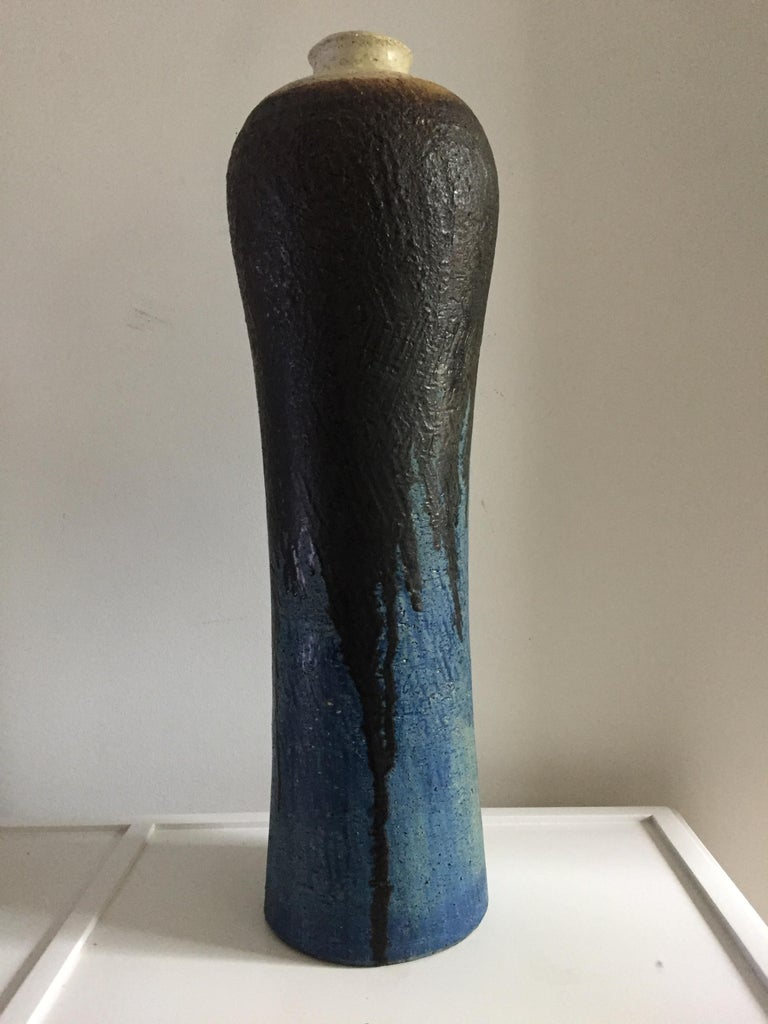 Monumental ceramic vase by Marcello Fantoni signed and numbered for Raymor ,tall and fluted at crème top with black glaze dripping down over a blue and turquoise hue's and texture.