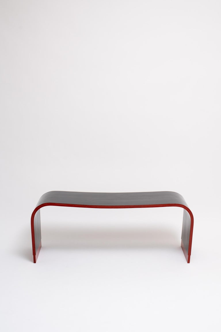 A lacquered black bentwood bench with accented edge in deep red by Marcello Piacentini, an influential architect and urban theorist in 1930s, Italy.