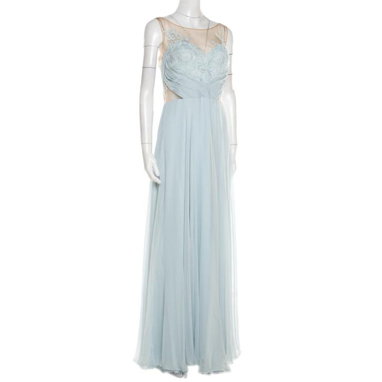 This Marchesa Notte gown is magnificent in appeal and shape, carefully tailored using blue silk and detailed with embroidery and sheer panels. A cinched waist and a floor-length hem make the gown ready to be yours.  Includes: The Luxury Closet