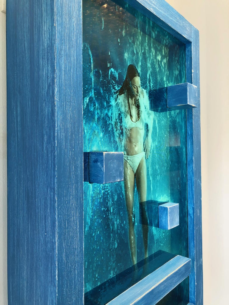 MARCK   'Waterfall' features 3 - 20 minute loops each of a different woman (changed by a button at base of the frame) under a continuous waterfall, interacting with blocks and a platform that exist both in the video and on the exterior of the