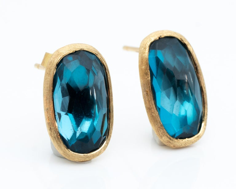 Absolutely stunning Marco Bicego designer earrings featuring blue topaz and 18 karat yellow gold  Made in Italy, circa 1990s  Iconic designer Marco Bicego Push Back earrings  Feature: Blue Topaz with visible facets, elongated oval shape  Crafted in