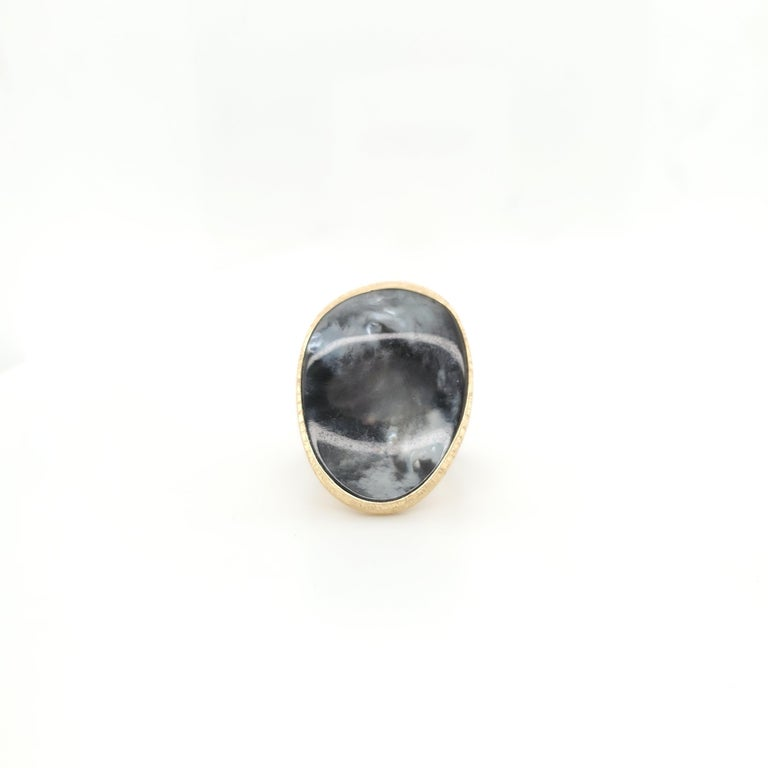 A handcrafted 18 karat yellow gold ring centering on a black mother of pearl stone and inspired by the lunaria flower. Made in Itlay. Signed Marco Bicego and marked 18K, serial no. 2616. Ring size 5. The ring does not come with original box or