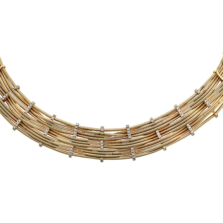 Sensational Marco Bicego collar necklace handcrafted in Italy in 18 karat yellow gold, featuring 75 round brilliant cut diamonds weighing approximately .56 carats total, G color, VS clarity. Pieces of gold are coiled into strands and woven between