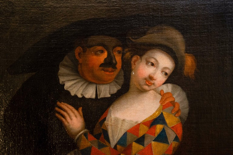 The painting depicts a gallant carnival scene. A woman dressed as a harlequin with the classic multicolored triangle dress is being embraced by a man dressed as Balanzone with his typical black dress and the mask hiding his face. The two are