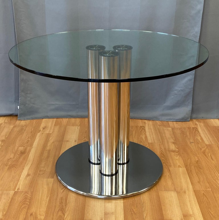 An impressive 1970 polished stainless steel and glass model 2532 Marcuso dining table by important and influential Italian architect and designer Marco Zanuso for Zanotta.  Modernist architectural form comprised of a trio of four inch diameter