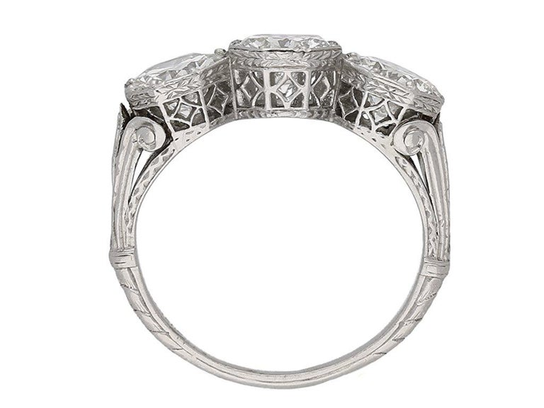 Three stone diamond ring. Horizontally set with three round old cut diamonds in open back grain set octagonal collets with an approximate combined weight of 3.00 carats, set to extremely ornate pierced open lattice collets with intricate pattern