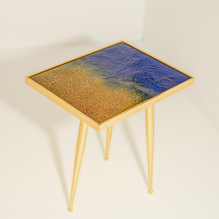 The Marea estate side table is the first installment of the Marea series depicting the four seasons via enameled tops handmade in Puglia. This iteration represents a Mediterranean summer with its dark blue waters and golden sand