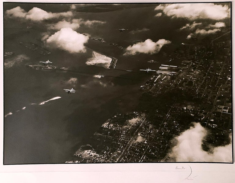 By MARGARET BOURKE-WHITE (1904-1971) - Airplanes and an aerial view of Palm Island, in the Caribbean. A warm-toned silver print with black border, the image measures 9 1/2 x 13 1/4 inches, the mount 14 x 19 inches with Bourke-White's stylized
