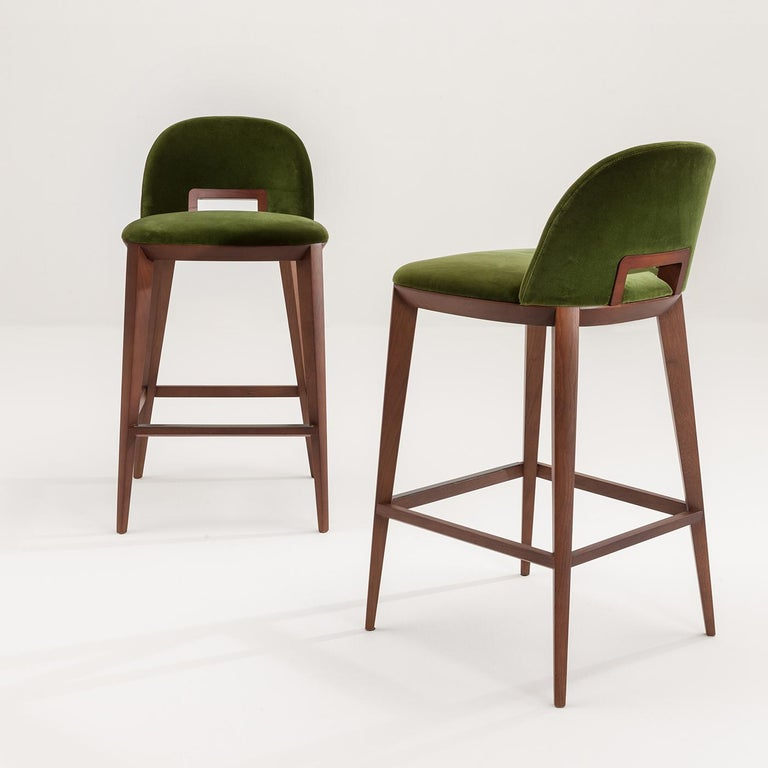 The Margaret Stool, in green velvet, has long, slender legs that intersect with the seat and backrest providing harmony and appeal. With a frame and handle in oak, the wood may be stained in rosewood, teak, wengè, black walnut, walnut and oak. The