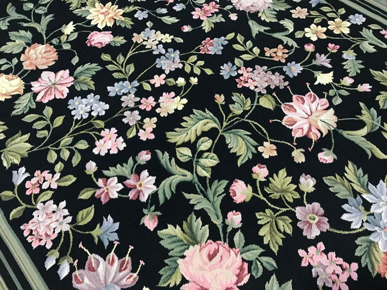 Green, teal and aqua vines laden with flowers in powder blue, lilac, rose, red, coral, yellow and gold cover a midnight-black ground. Made with fine quality wool yarns this handmade needlepoint rug has many subtle color shades similar to antique