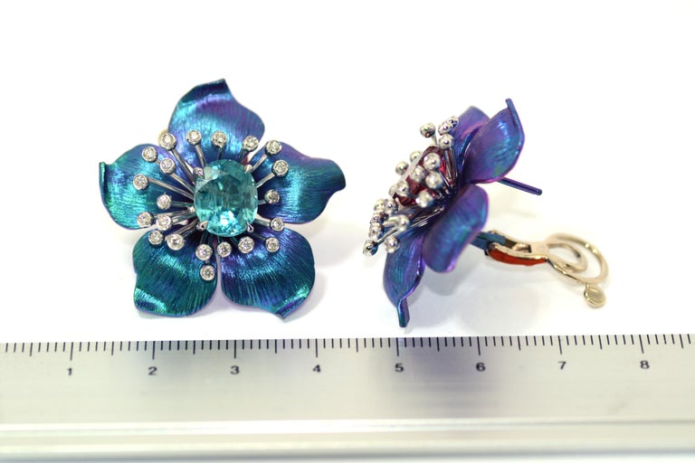 Handcrafted in Italy in Margherita Burgener factory, the Happy Flower earrings are titanium made, centering a 18kt white gold spray motif, set with diamonds, highlighting a central faceted oval natural paraiba blue zircon.  18kt white  gold g 9,70