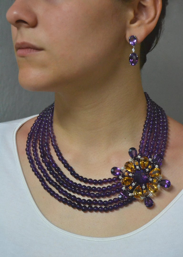 Handcrafted in Italy, In Margherita Burgener factory, based in Italy. The necklace is realised by 5 strands of round natural amethyst and it features the e precious detail of a colorful brooch.  The brooch can be easily detached and can be worn