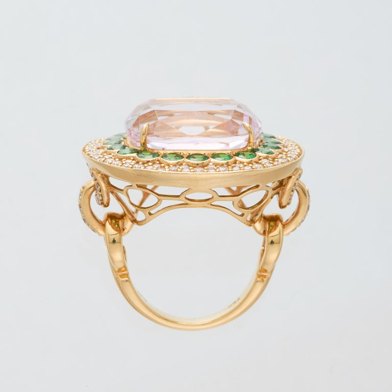 Margot McKinney 18 Karat Yellow Gold Ring set with 1 cushion cut Pink Kunzite weighing in total 23.43ct. The Kunzite is surrounded by a single border of 20  Tsavorites weighing in total 2.51ct and tapering to a double row border of 100 brilliant cut