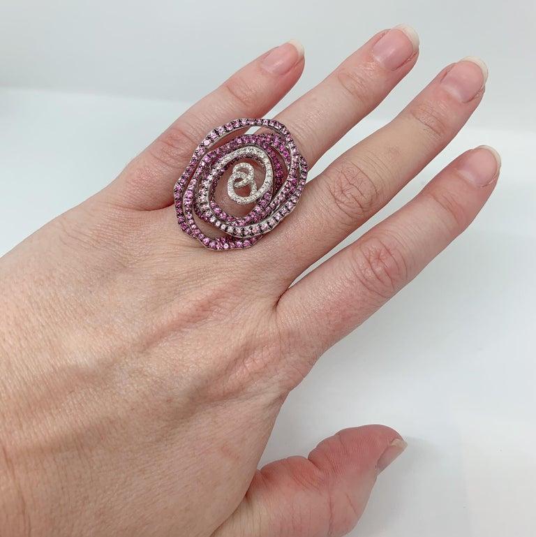 Margot McKinney 18 Karat White Gold Swirl Ring set with 0.27 carat White Diamonds and 3.14 carat Pink Sapphires.  Ring Size USA 6.5 (UK/AU Size M).