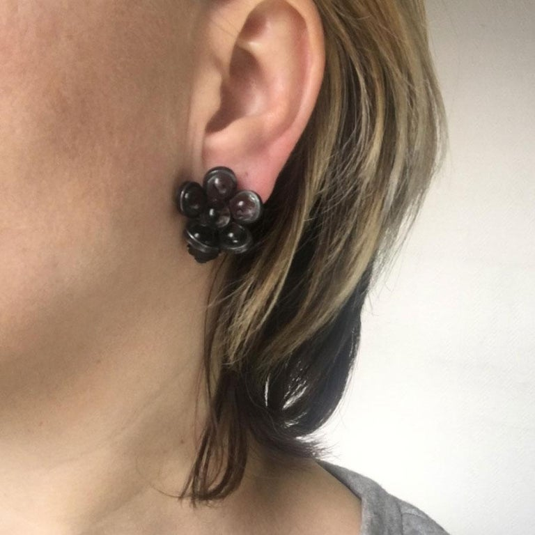 Marguerite de Valois flower clip earrings in transparent anthracite glass paste. Ruthenium-colored metal. Mint condition. Brand initials engraved on the back of each buckle Entirely handmade in France, by its artisan jewelers who have worked in the