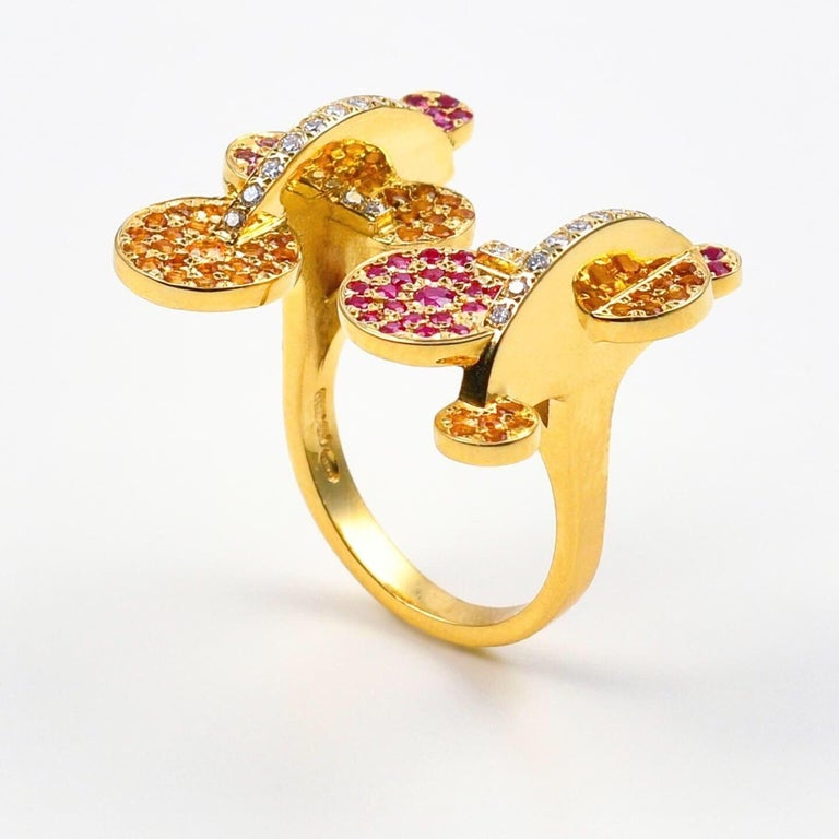 The 'Exploding Disk', ring is crafted in 18k gold, hallmarked in Cyprus. This stunning, open, sculptural ring, comes in a highly polished finish and features Rubies 0,35 Cts, Rhodolites 0,12 Cts, Madeira Citrines 0,45 Cts and Diamonds 0,24 Cts. The