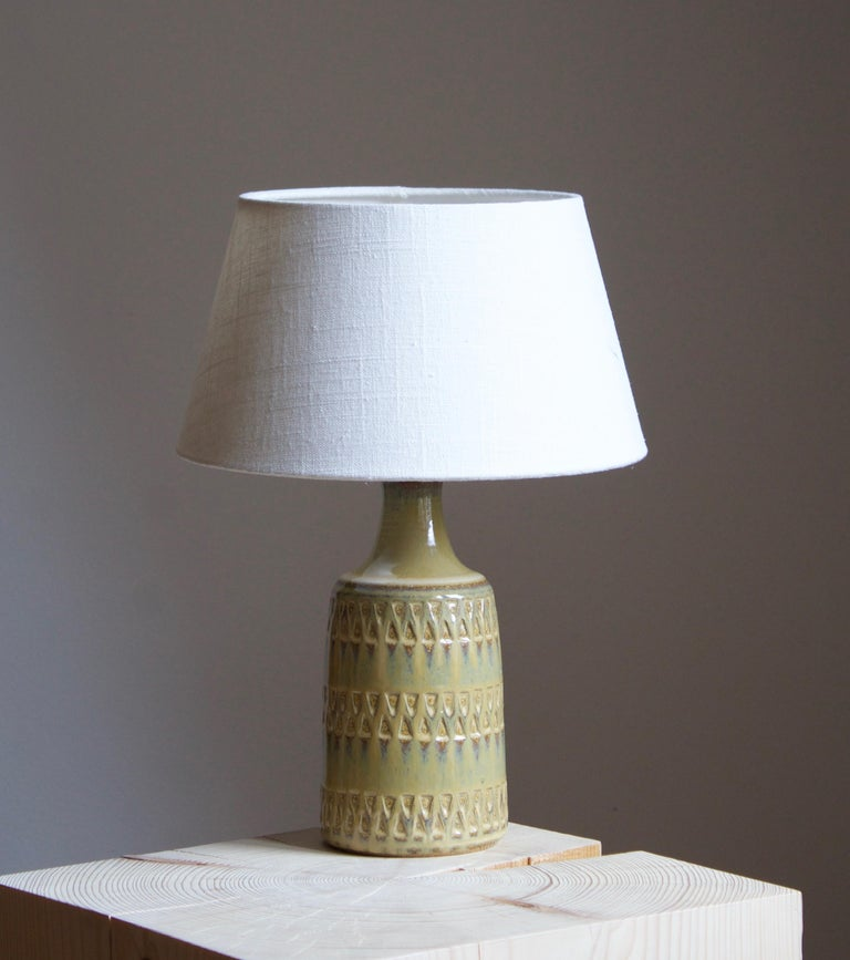A table lamp produced by Søholm Keramik, located on the island of Bornholm in Denmark. Features a highly artistic glazed and incised decor.   Sold without lampshade. Stated dimensions exclude the lampshade.  Other designers of the period include