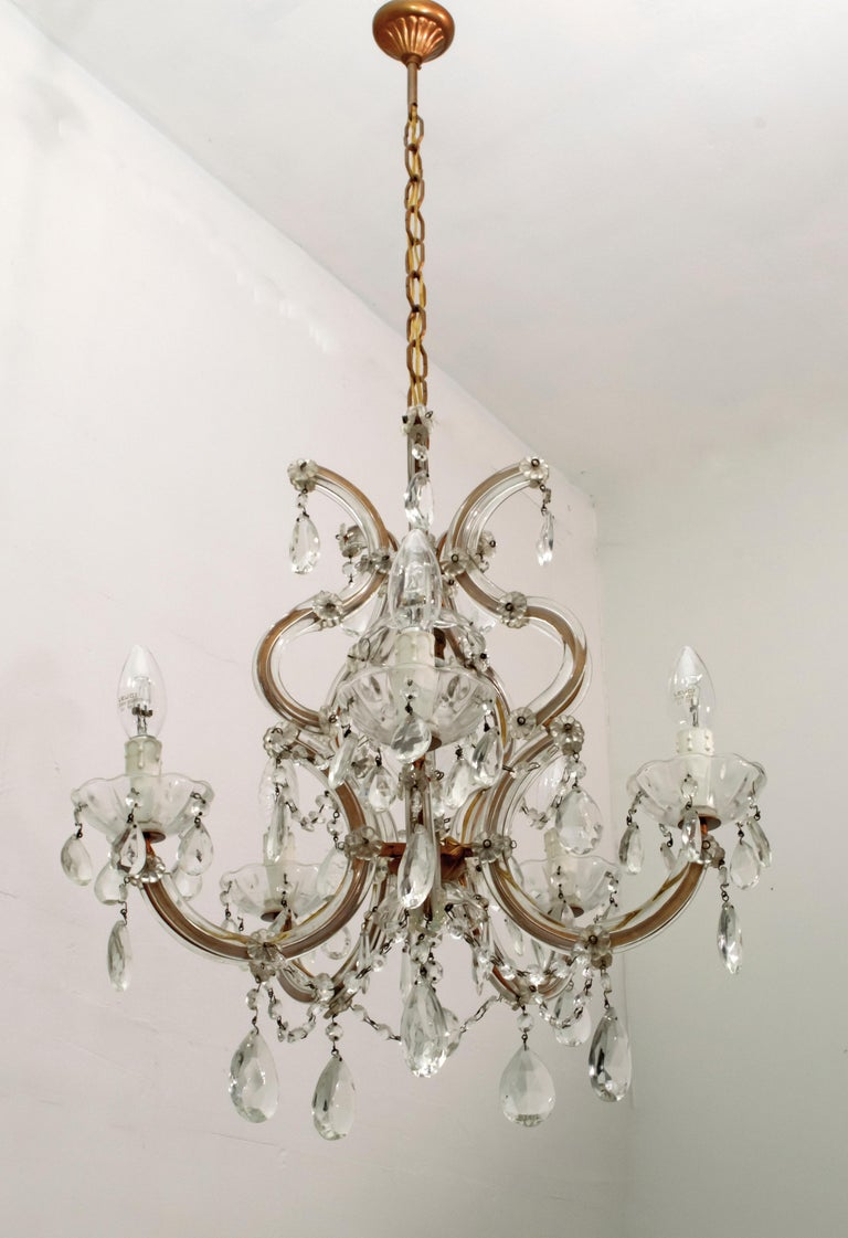 A delightful 6-light Maria Theresa chandelier in Italian crystal and gilded metal with serpentine arms, each candle light with hanging pendants and decorative bobeches.
