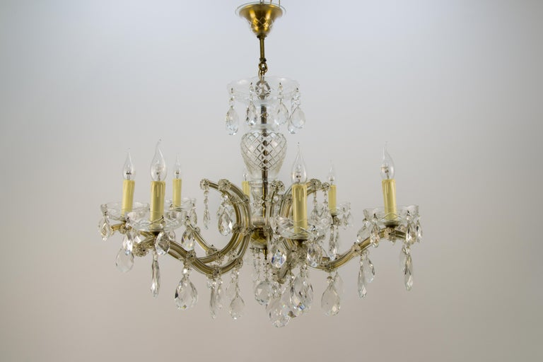Beautiful Italian Maria Theresa style eight-light crystal chandelier. Brass and metal frame covered in glass with hanging crystal pendants, eight sockets for E14 size light bulbs. Dimensions: Diameter 91 cm / 35.82 in; height 83 cm / 32.67 in.