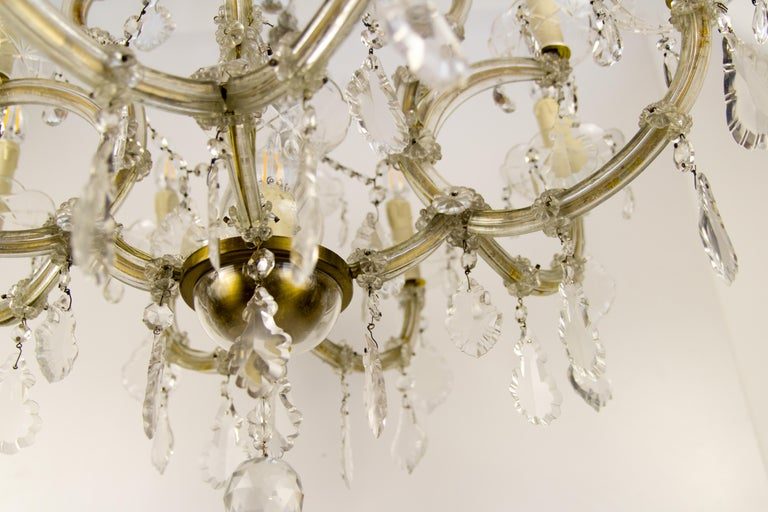 Beautiful Italian Maria Theresa style thirteen-light crystal chandelier. Brass and metal frame covered in glass with hanging crystal pendants, thirteen sockets for E14 light bulbs. Dimensions: Diameter 77 cm / 30.31 in; height 101 cm / 39.76 in.