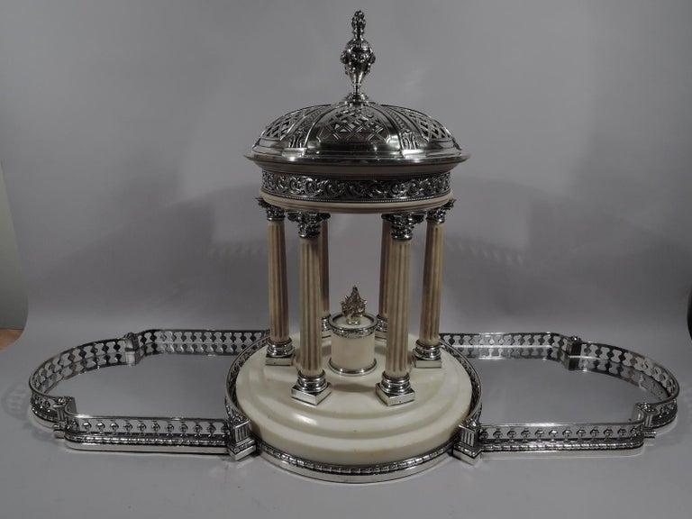 French 950 silver and marble centerpiece based on Marie Antoinette's garden folly, the Temple d'Amour at Versailles.   Round stepped marble base with silver imbricated leaf-and-berry border. Six fluted columns with silver base and Corinthian