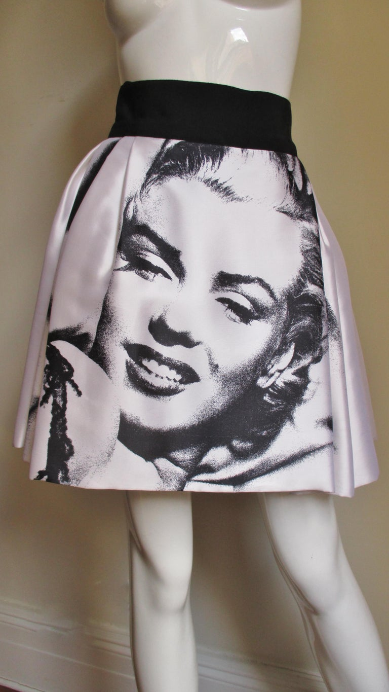An amazing screen print of iconic sex symbol Marilyn Monroe on the front and back of a white silk skirt from Dolce and Gabbana. The skirt has a 3