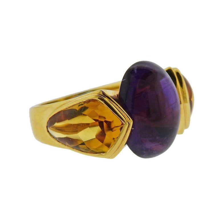 18k yellow gold ring by Marina B, set with 16.1mm x 11.3mm amethyst cabochon, with citrines and peridots around. Ring size - 6.5, ring top is 16mm wide. Weight is 12.8 grams. Marked Marina B, MB, 179015, 750.