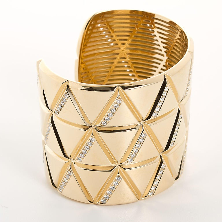A sleek 18k gold and diamond torque bangle by Marina B with a geometric stacked triangle motif and set with 3.84 carats of white diamonds. Bangle size 6.25.  No. TMWJ-190506-1