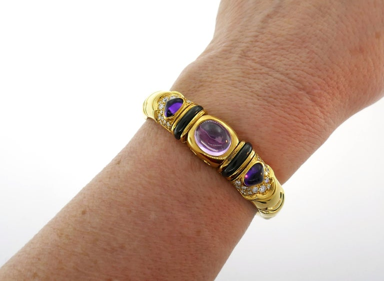 Colorful and chic bangle created by Marina B in 1980s. Elegant and wearable, the bracelet is a great addition to your jewelry collection. Features an oval cabochon pink tourmaline set in 18 karat yellow gold accented on each side with a pear
