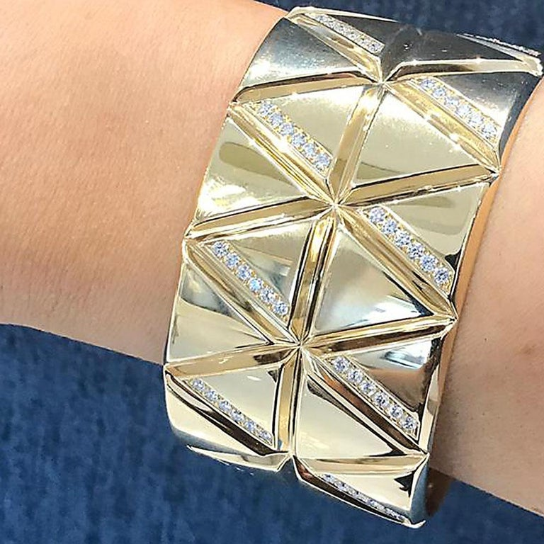 A sleek 18k gold and diamond torque bangle by Marina B with a geometric stacked triangle motif and set with 2.25 carats of white diamonds. Bangle size 6.25.  No. TMWJ-190506-2