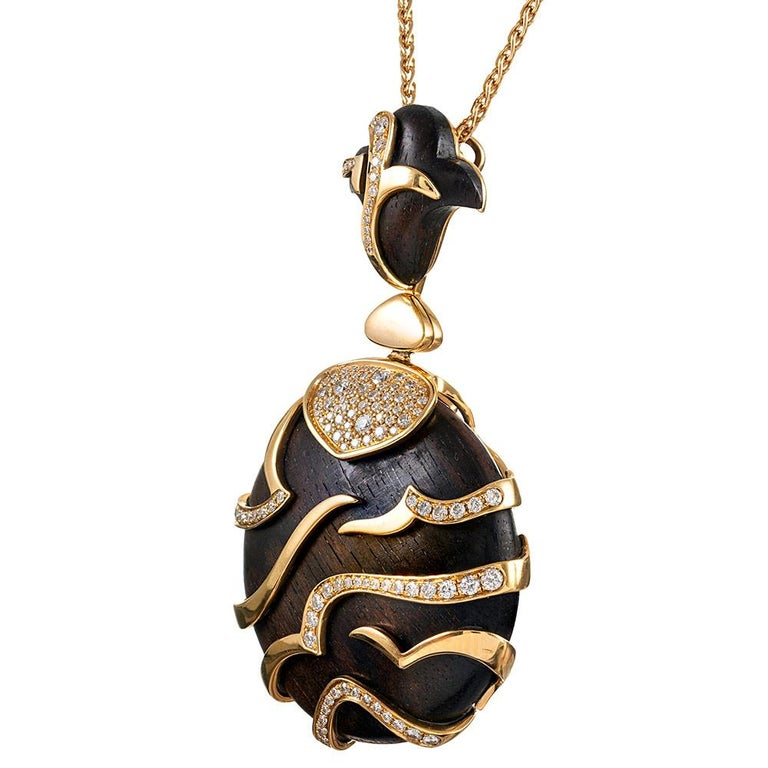 A substantial and exotic creation, compliments of Marina B, the piece is designed as an ebony disc, suspended from a sculpted bale and decorated with golden tiger stripes and brilliant white diamonds. The pendant has been embellished with 1.05