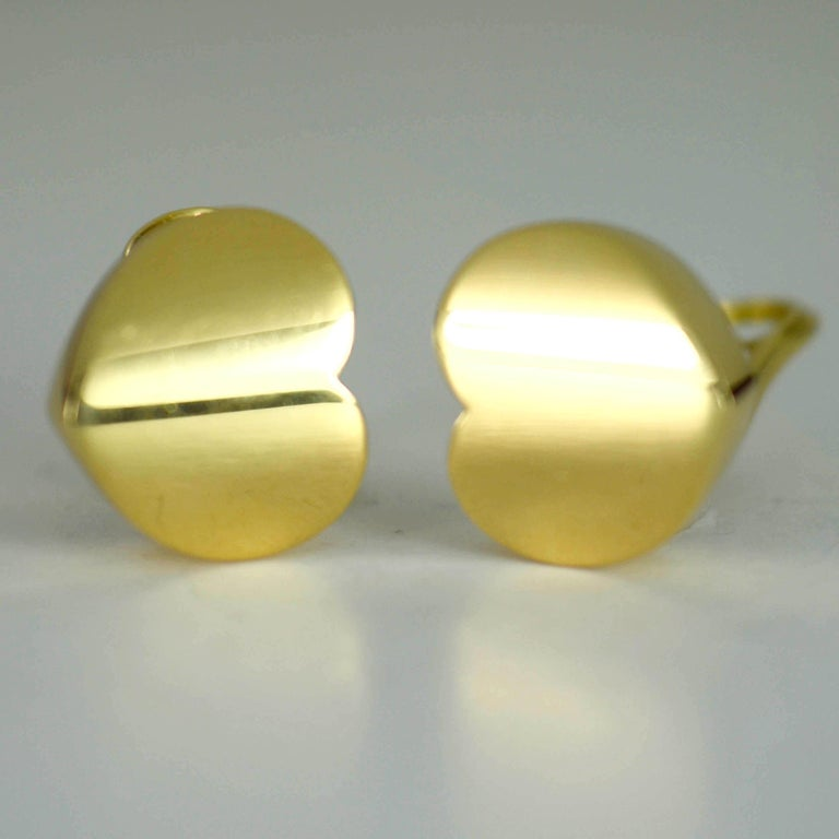A pair of 18 karat yellow gold ear clips by Marina B designed as a heart worn sideways on each ear. The earrings are signed 'Marina B', marked 'MB', numbered 2239002 and have control marks for 18 karat gold and Italian manufacture.  Height: 1.8cm,