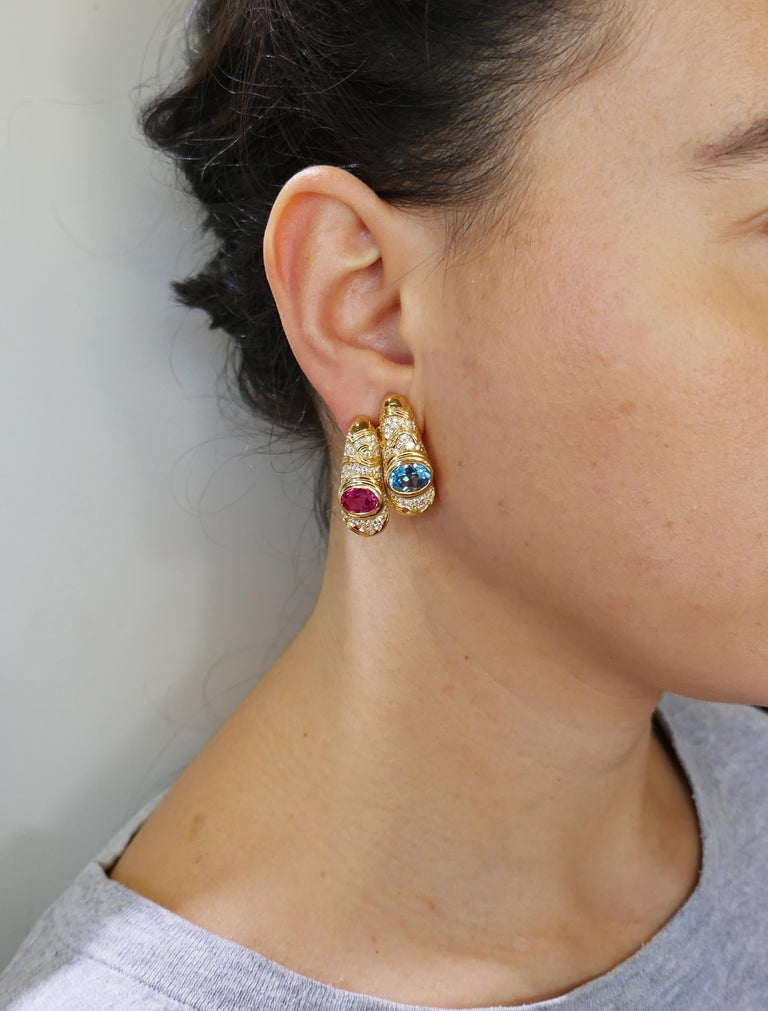 Colorful and chic double hoop earrings created by Marina B in 1980s. They definitely make a statement! Elegant and wearable, the earrings are a great addition to your jewelry collection. The earrings feature an oval faceted blue topaz and purple