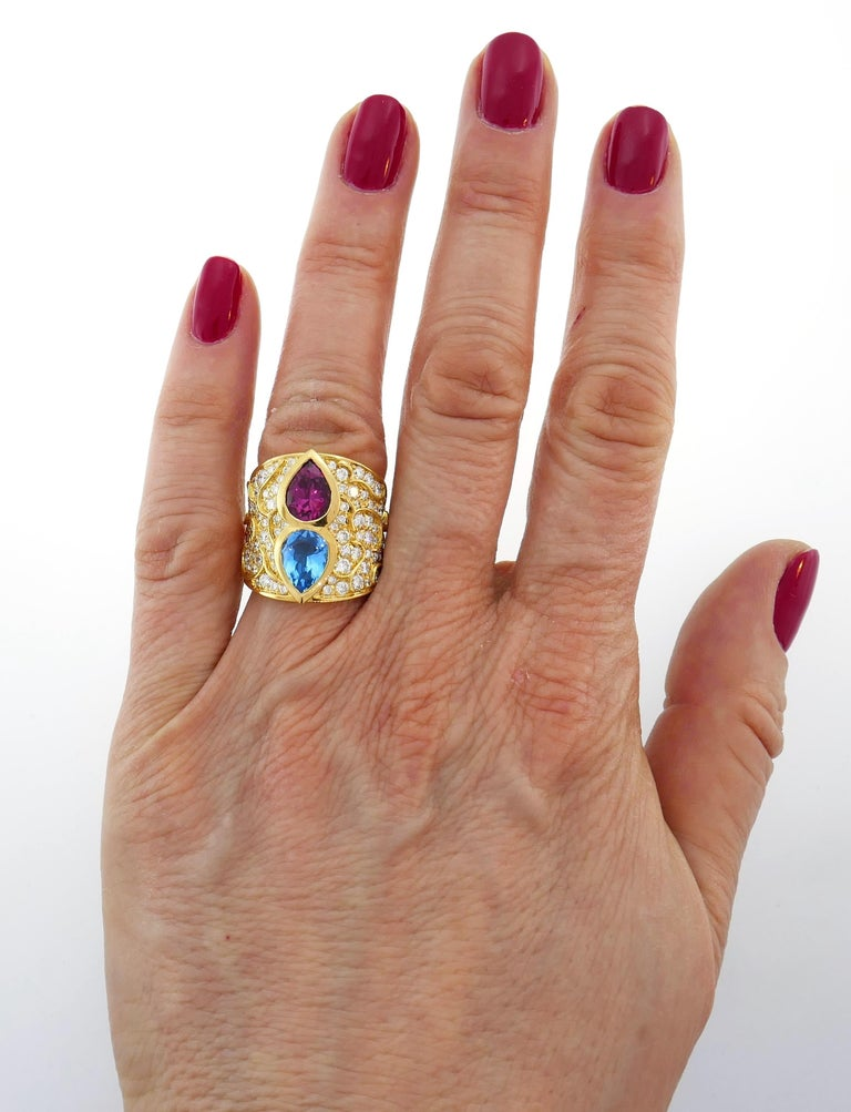 Colorful and chic cocktail ring created by Marina B in 1980s. It definitely makes a statement! Elegant and wearable, the ring is a great addition to your jewelry collection. The ring features a pear-shape blue topaz and purple tourmaline set in 18