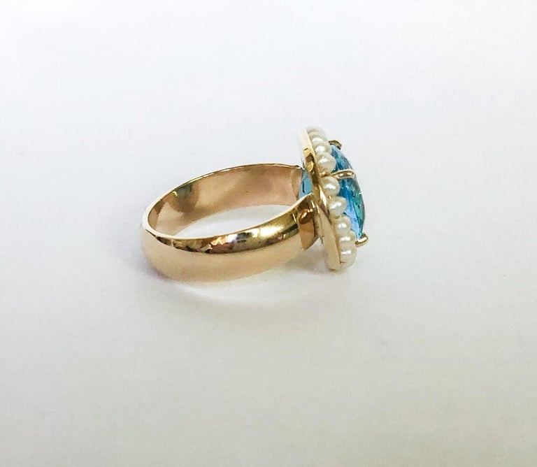 This elegant ring is made of a 6.55 carat Sky Blue Topaz gemstone, measuring 10x12 mm. Surrounding the gemstone are 20 2mm seed pearls, making the ring 15x17 mm in total. The band is made of 14k gold and is 0.5 cm wide. The ring is size 6.  This