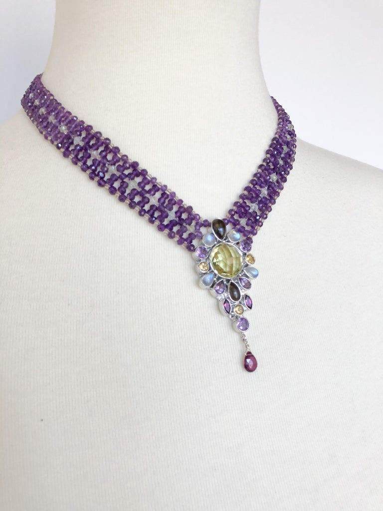 This standout necklace is made with amethyst citrine and yellow/blue topaz beads. The centerpiece is made with a large citrine stone, surrounded by small garnet, opal and citrine stones, with a small garnet bead hanging from the centerpiece. This