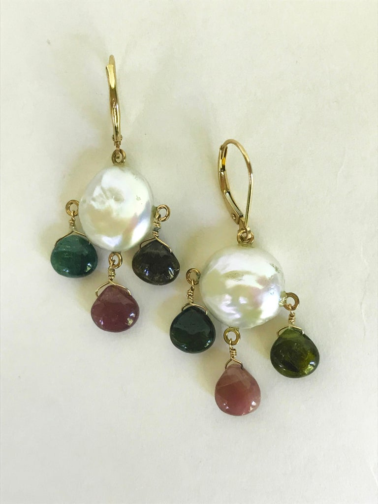 These beautiful earrings are made from 14k yellow gold wiring and Lever-back. The multi-color tourmalines drop from a flat coin shaped white pearl. Inspired by a Autumn themed color palate, these elegant yet whimsical earrings are intentionally