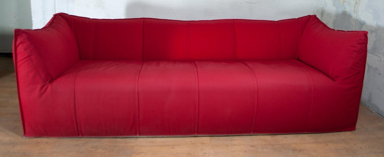 Mario Bellini designed Le Bambole for B&B Italia in 1972, armchairs and sofas shaped in their entirety as large cushions. Combining extraordinary comfort and style, this Tribambola sofa and the Pouf are upholstered in a vibrant red canvas, which is
