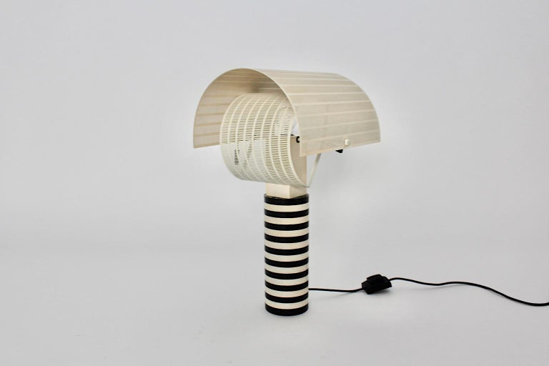A Mario Botta black and white vintage table lamp which was made 1980s Italy for Artemide. The iconic table lamp shows two adjustable perforated metal shields to spread the light shine. The designer name is labeled at the base. It is a perfect