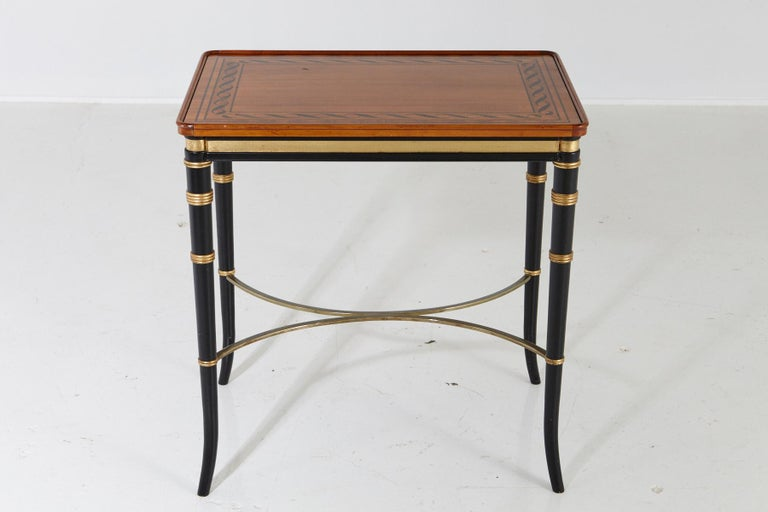Beautiful eye-catching Regency style end table with paint decorated mahogany top and ebonized apron and legs with gilt rings, splayed feet, and brass reverse