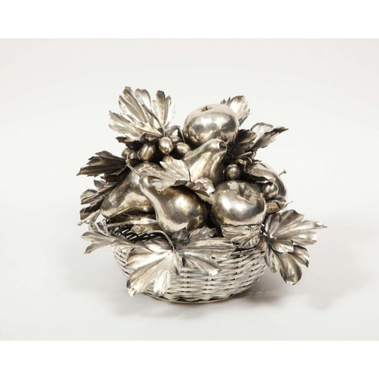 Mario Buccellati, an Italian silver fruit basket centerpiece    The woven sterling silver basket, topped by a removable textured and sculpted sterling silver arrangement of fruits    The grape stem acts as the handle, 10