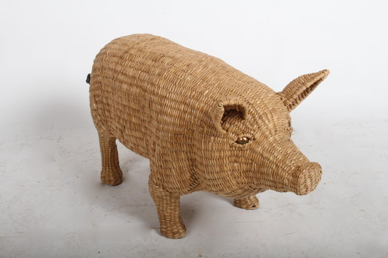 Rarely seen and highly sought after Mario Lopez Torres wicker pig sculpture. Wicker woven over iron frame, copper eyes and iron tail. Signed and dated on a brass medallion found on the underside chest of the pig: Mario Lopez Torres, Tzumindi, Hecho