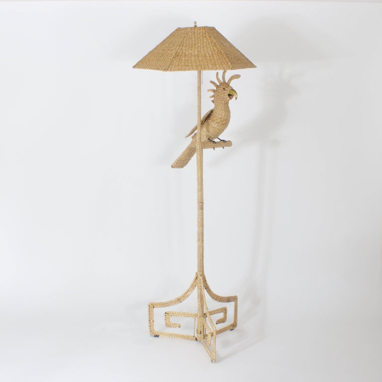 Amusing Cockatoo wicker or reed floor lamp with matching wicker shade. Featuring a brass and copper beak and copper eyes, having a Greek key three-legged base. All executed in a tight disciplined weave. Signed Mario Torres 1974 made in Mexico.