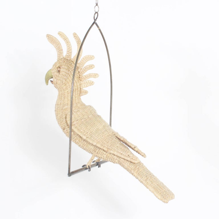 Amusing midcentury Mario Torres wicker Cockatoo perched on a metal swing. Having a brass face and beak. He appears to be saying something cheeky.