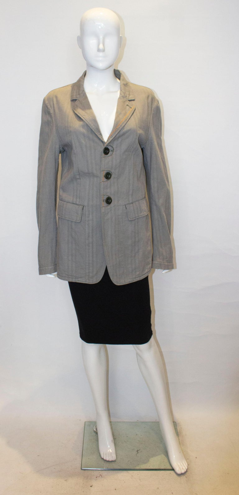 A chic cotton jacket by Marithe Francois Girbaud.  The jacket is in an interesting mix pattern fabric. It is unlined, with  three button front opening, two large pockets on the front, a one button cuff and 7 '' slit at the back.