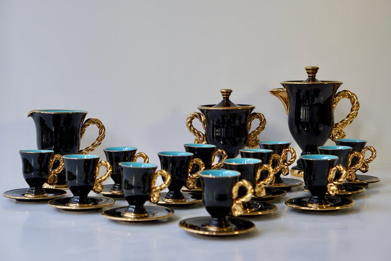 The beautiful set comprised of a tea or coffee pot, a cream jug and a sugar bowl with lid and thirteen cups and saucers, each piece with gilded borders.