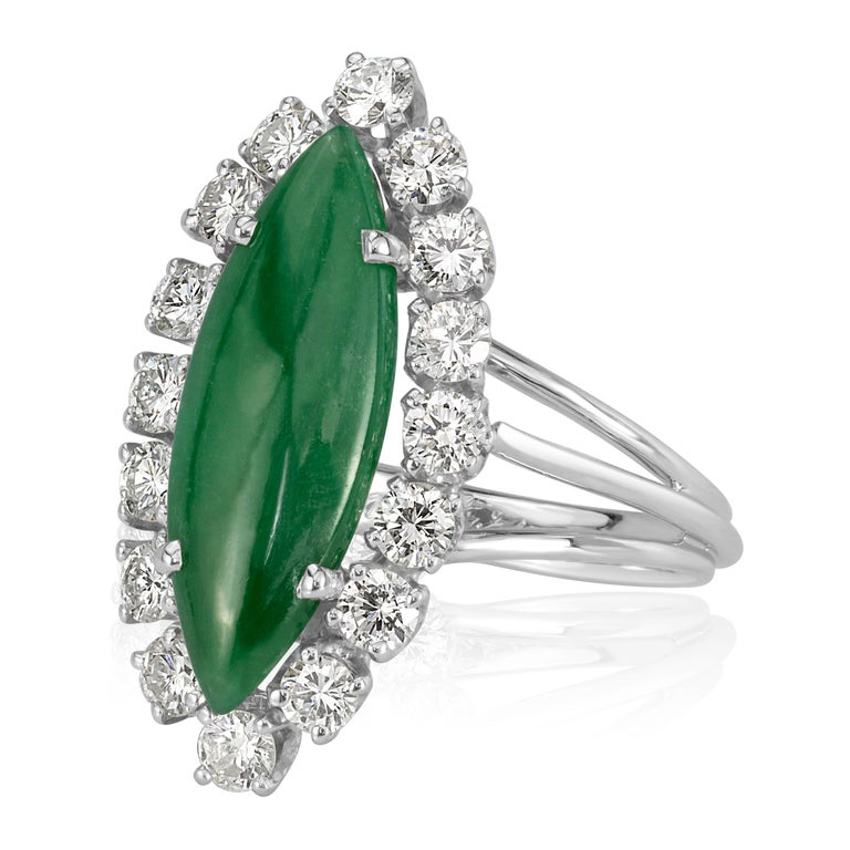 This unique estate piece dates back circa 1969 and has the original engraving inside. It showcases an elongated jade cabochon at the center complimented by a shimmering halo of round brilliant cut diamonds. They are set on a high polish, 18k white