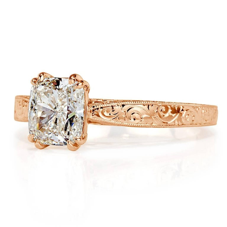 This stunning solitaire diamond engagement ring showcases a beautiful 1.52ct cushion cut center diamond, GIA certified at K-VS1. It is set in a beautiful 18k rose gold setting featuring delicate hand engraved details throughout. The side of the ring