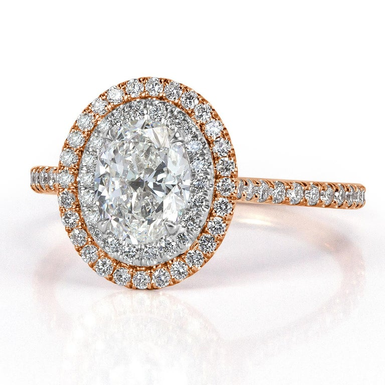 This two-tone diamond engagement ring features a ravishing 1.00ct oval cut center diamond, GIA certified at F-VS2. It is accented by a double halo of round brilliant cut diamonds as well as one row of shimmering diamonds micro pavé set around the