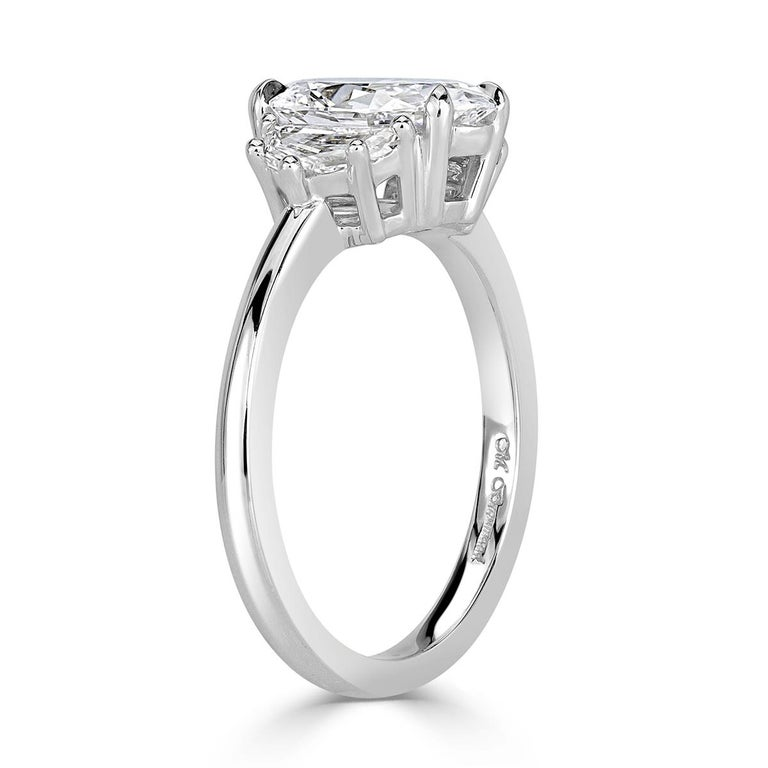 This unique, three-stone oval cut diamond engagement ring features a gorgeous 1.61ct oval cut center diamond, GIA certified at D-VVS2. It has amazing measurements of 10.47 x 6.49 mm which means it is very elongated and looks much larger than its